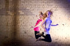 Teenage girl jump against brick wall background Stock Photos