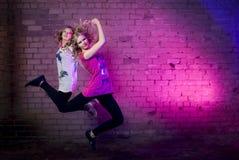 Teenage girl jump against purple wall Stock Image