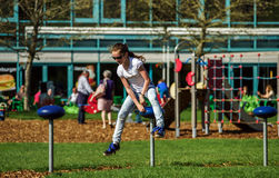 Teenage girl jumping on child playground Royalty Free Stock Images