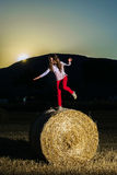 Teenage girl jumping from the haystack Royalty Free Stock Photography