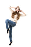 Teenage girl jumping with joy. Beautiful happy smiling teenage girl wearing jeans, jersey and knitted hat jumping with delight, dancing, isolated Royalty Free Stock Image