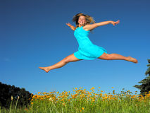 Teenage girl jumping in the meadow. In summer day stock images