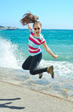 Teenage girl jumping by the Mediterranean beach Stock Photography