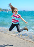 Teenage girl jumping by the Mediterranean beach Royalty Free Stock Image