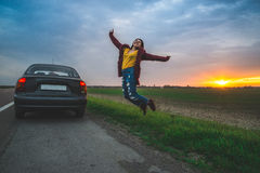 Teenage girl jumping on open road near car Stock Photos