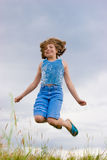 Teenage girl jumping over green grass Royalty Free Stock Photo