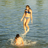 Teenage girl jumping into the river Stock Image