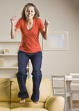 Teenage girl jumping on sofa Royalty Free Stock Photography