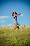 Teenage girl jumping on summer field Stock Image