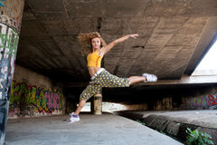 Teenage girl jumping. Wall with graffiti Stock Photo