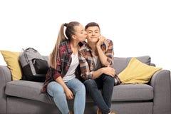 Teenage girl kissing a boy on a sofa stock photos