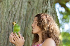 Teenage Girl Kissing Toy Frog Against Tree Trunk Stock Photos