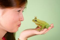 Teenage girl kissing Tree frog Litoria infrafrenata with a crown on his head Stock Image