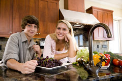 Teenage girl in kitchen with younger brother Royalty Free Stock Image