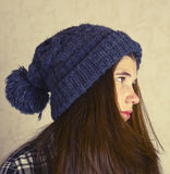 Teenage girl in knitted blue hat with pompom. Close up portrait. Teen girl in winter hat Royalty Free Stock Photos
