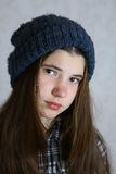 Teenage girl in knitted blue hat with pompom. Close up portrait. Teen girl in winter hat Stock Images