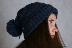 Teenage girl in knitted blue hat with pompom. Close up portrait. Teen girl in winter hat Stock Photo