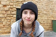 A teenage girl with a knitted hat. Making funny faces. Behind an old building in the old city of Akko Acre, Israel royalty free stock images