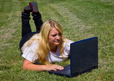Teenage girl with laptop computer outdoors. Teenager concentrates as she uses her laptop in the great outdoors Royalty Free Stock Images