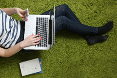 Teenage girl with laptop. A young woman works on her laptop on the floor and holding phone in the other hand Royalty Free Stock Images