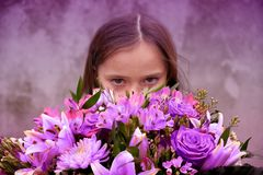 Teenage girl with large bunch of colorful flowers. Teenage girl with a large hand-tied bouquet of pink and purple flowers saying I am sorry stock photos