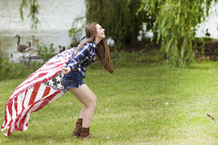A teenage girl laughing with delight while holding American flag scarf. Stock Image