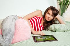 Teenage girl laying in bed with tablet computer Stock Photo
