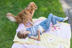 Teenage girl laying down in the yard with her dog Stock Photography