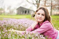 Teenage girl laying flower field barn background Stock Photo