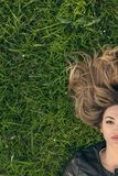 Teenage girl laying in grass Stock Photography