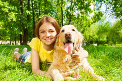 Teenage girl laying with her pet dog in park Royalty Free Stock Photos