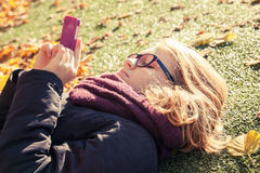 Teenage girl laying in park and using cellphone. Caucasian blond teenage girl in black jacket laying in autumnal park and using cellphone for messaging in social Royalty Free Stock Images