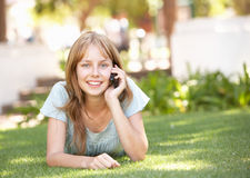Teenage Girl Laying In Park Using Mobile Phone Royalty Free Stock Images