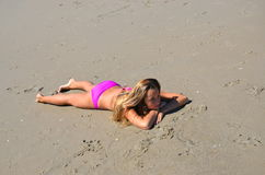 Teenage girl laying in sand wearing pink bikini Royalty Free Stock Photos