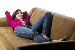 Teenage girl laying on a sofa Stock Image