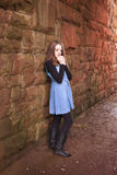 Teenage girl leaning against an old wall with her hands under he Royalty Free Stock Photography