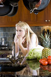 Teenage girl leaning on kitchen counter thinking Stock Photo