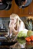 Teenage girl leaning on kitchen counter thinking Stock Photo