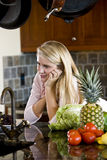 Teenage girl leaning on kitchen counter thinking Stock Photography