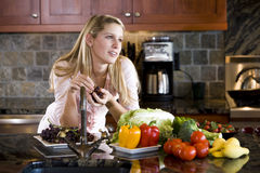 Teenage girl leaning on kitchen counter thinking Royalty Free Stock Photos