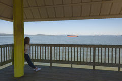 Teenage girl leans on post while looking at ships in the Columbia River Stock Image