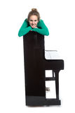 Teenage girl lies on piano in green shirt Stock Images