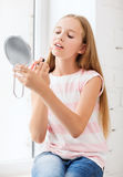 Teenage girl with lip gloss and mirror Royalty Free Stock Photo