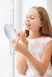 Teenage girl with lip gloss and mirror Stock Photos