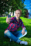 Teenage girl listening music and making selfie photo with smart Royalty Free Stock Image