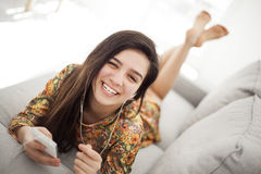 Teenage girl listening music through mobile phone Stock Images