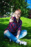 Teenage girl listening music and thumbs up in park Royalty Free Stock Image