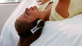 Teenage girl listening music while using mobile phone. In bedroom stock video footage