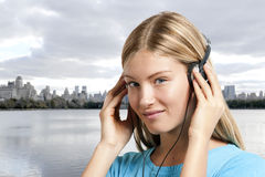 Teenage girl listening to the music. Manhattan skyline in the background Stock Photos