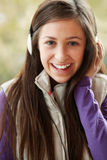 Teenage Girl Listening To Music. Teenage Girl Wearing Headphones And Listening To Music Wearing Winter Clothes Royalty Free Stock Images